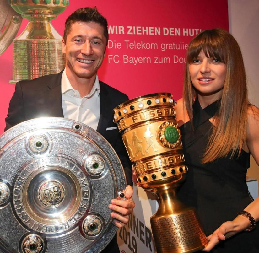 ARCHIVE - 25.05.2019, Berlin: Soccer, DFB Cup Final, RB Leipzig - FC Bayern Munich: Robert Lewandowski and his wife Anna Lewandowska pose with the DFB Cup and championship trophy on the final night of 2019 at the official banquet of FC Bayern Munich.  Lewandowski's wife Anna is the most important advisor for Europe's footballer of the year.  The star striker of FC Bayern Munich always analyzes his games with her.  She enthuses: