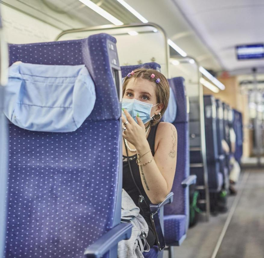 A young Mv_dchen, about 20 years, traveling with the Deutsche Bahn under corona conditions in a train in Mv_nchner Hauptbahnhof.  |  Usage worldwide