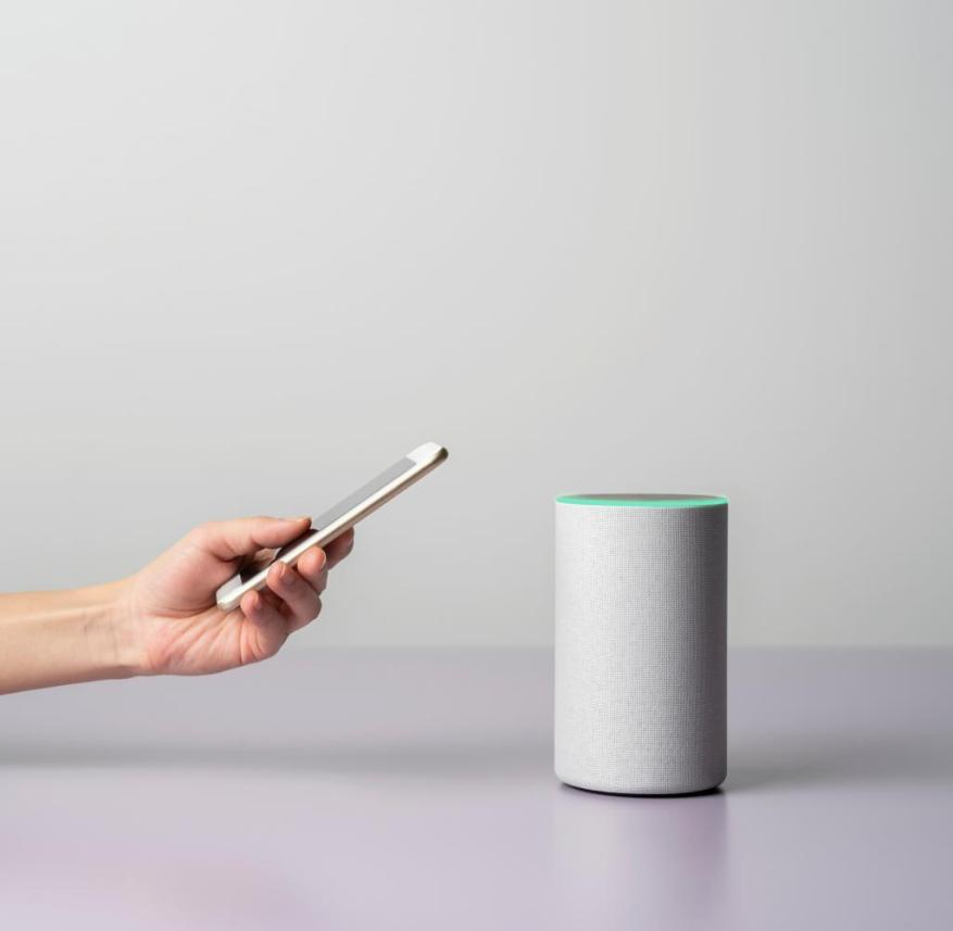 Woman using a Smart speaker with smart phone.