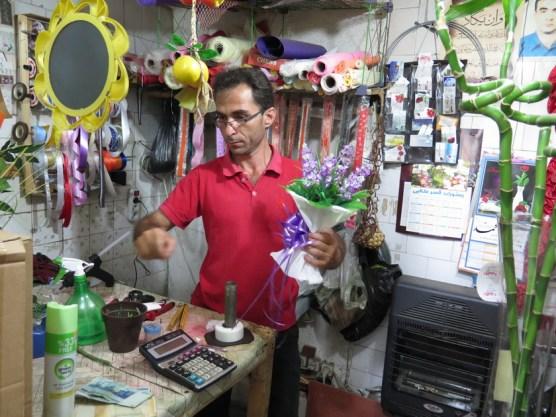 Florist, der mit viel Liebe einen Plastikblumenstrauß bindet