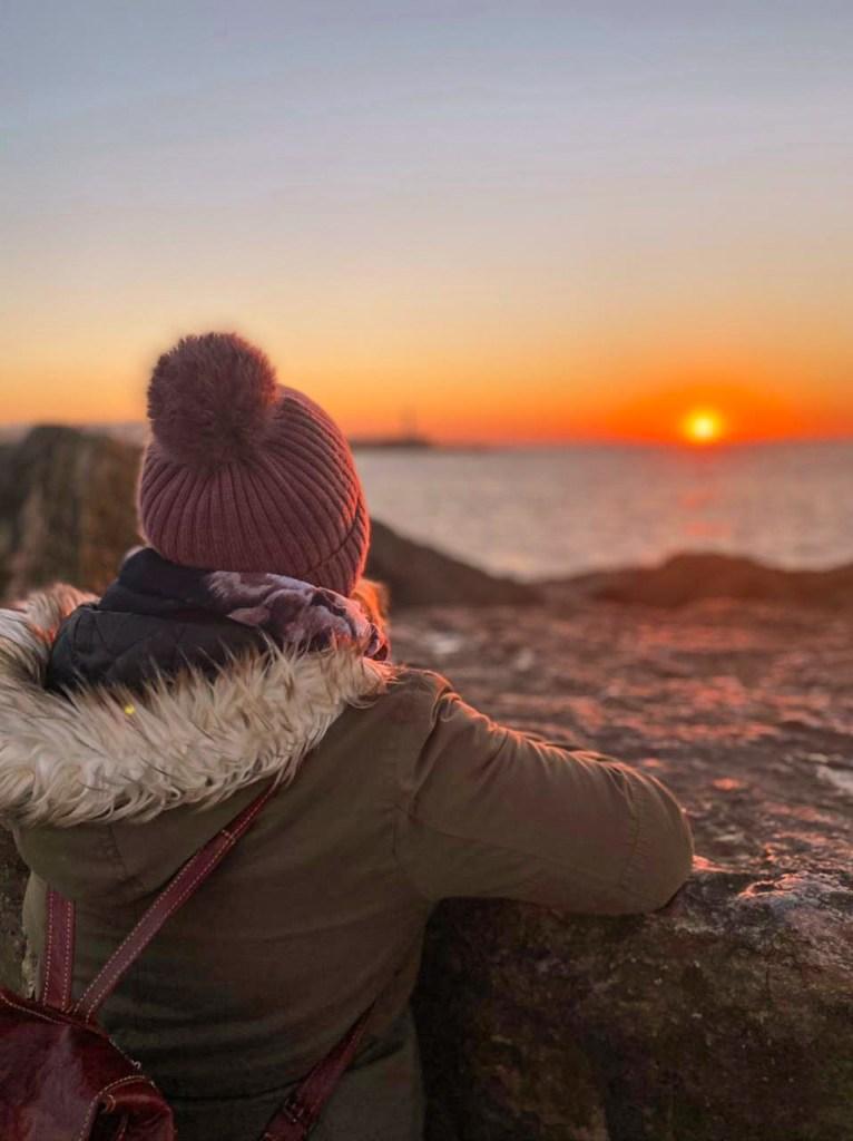 Frau schaut auf den Sonnenuntergang über dem Meer