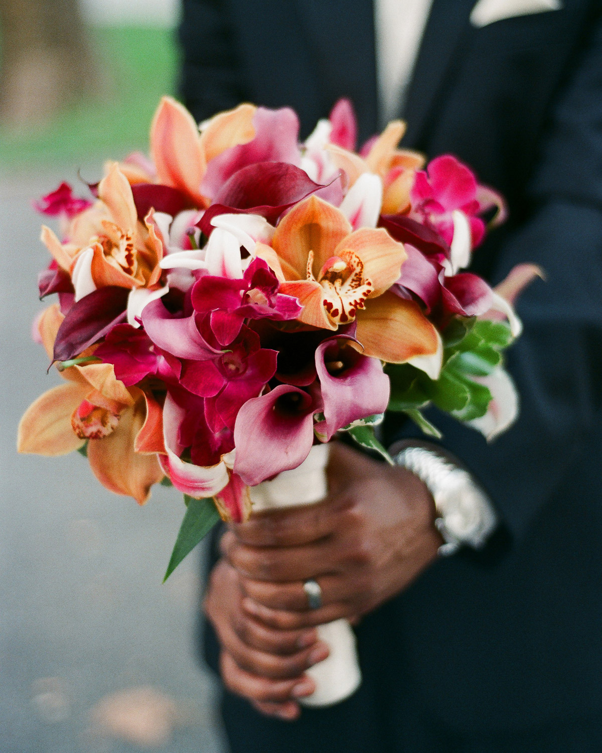 groom holding bridal bouquet of colorful flowers by wendy g photography