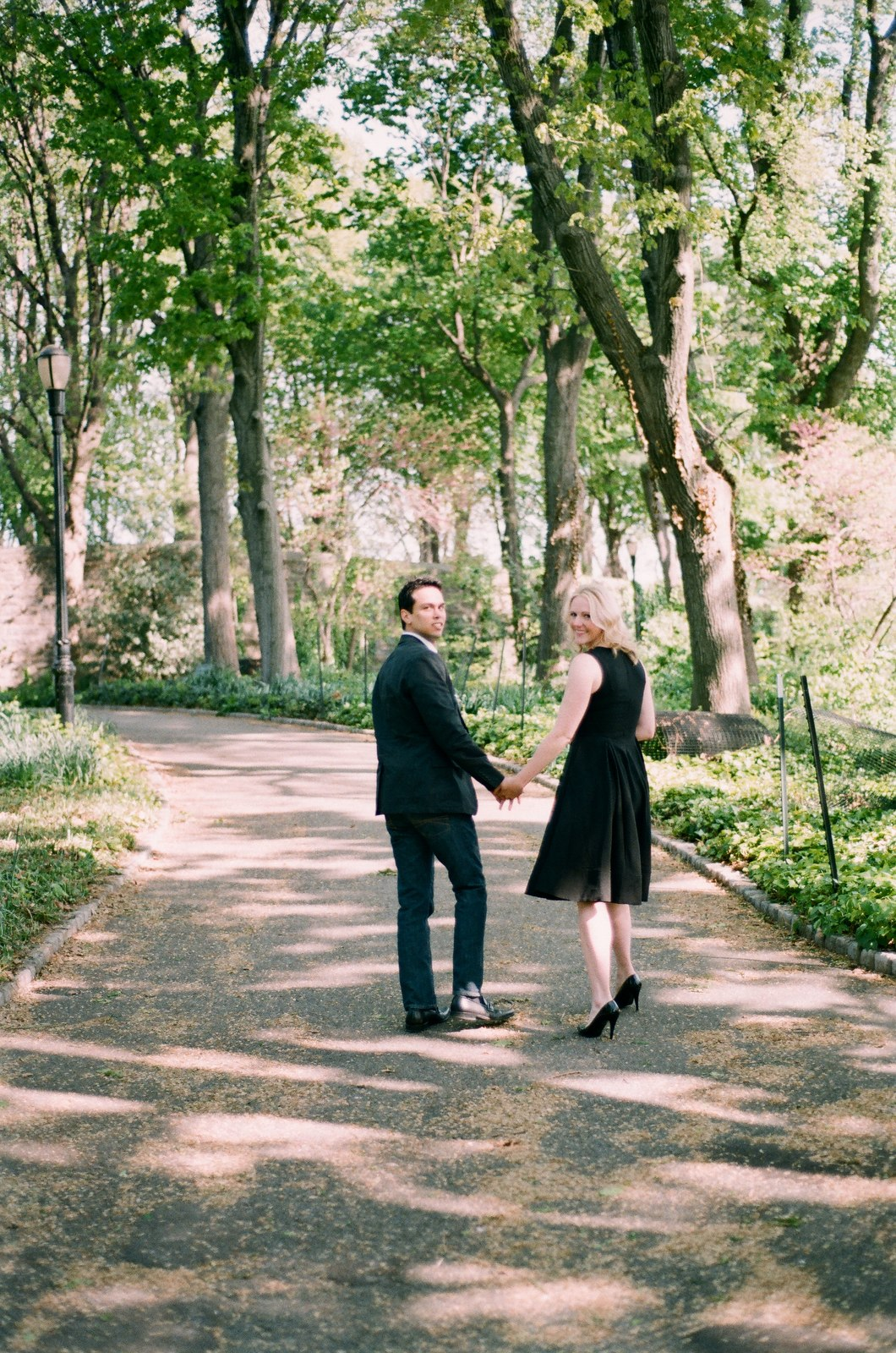 engaged couple looking backward on pathway at park