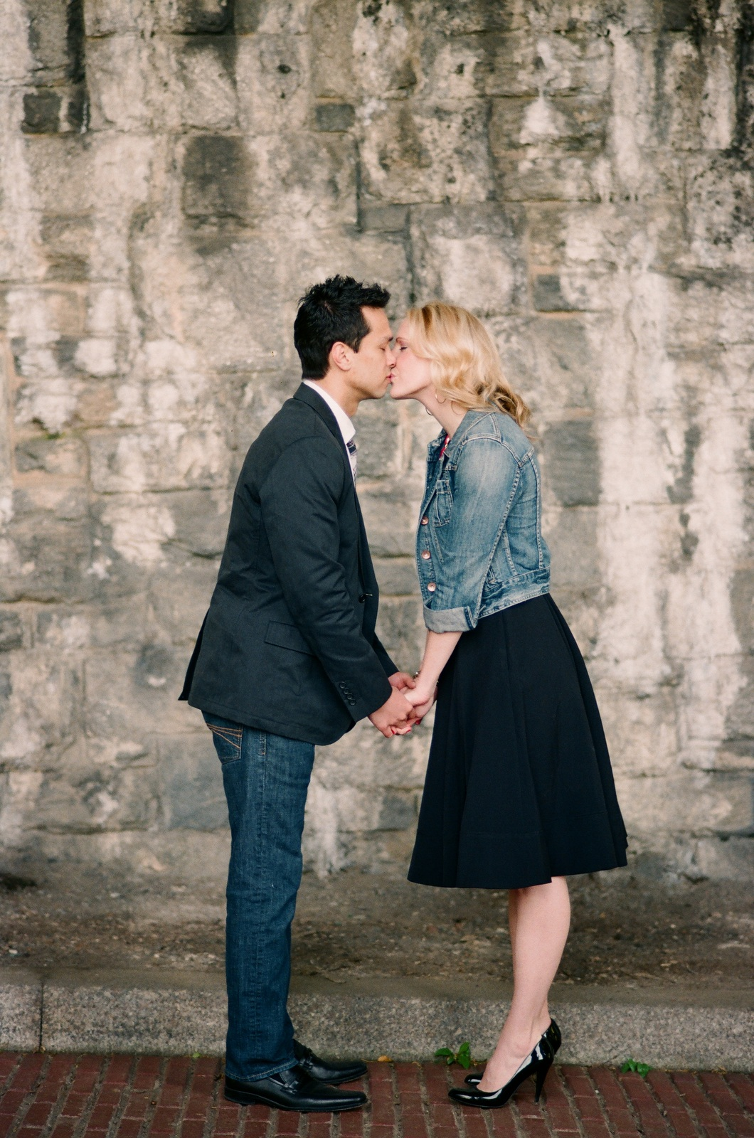 engaged bride and groom kissing at fort tryon park ancient ruins