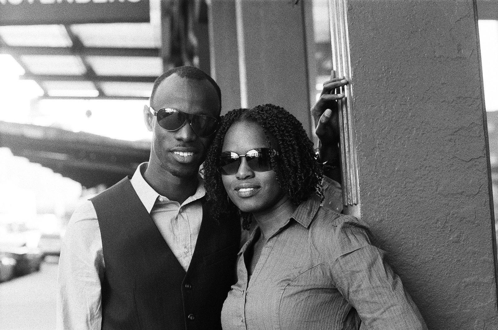 black and white photo of engaged couple smiling wearing sunglasses