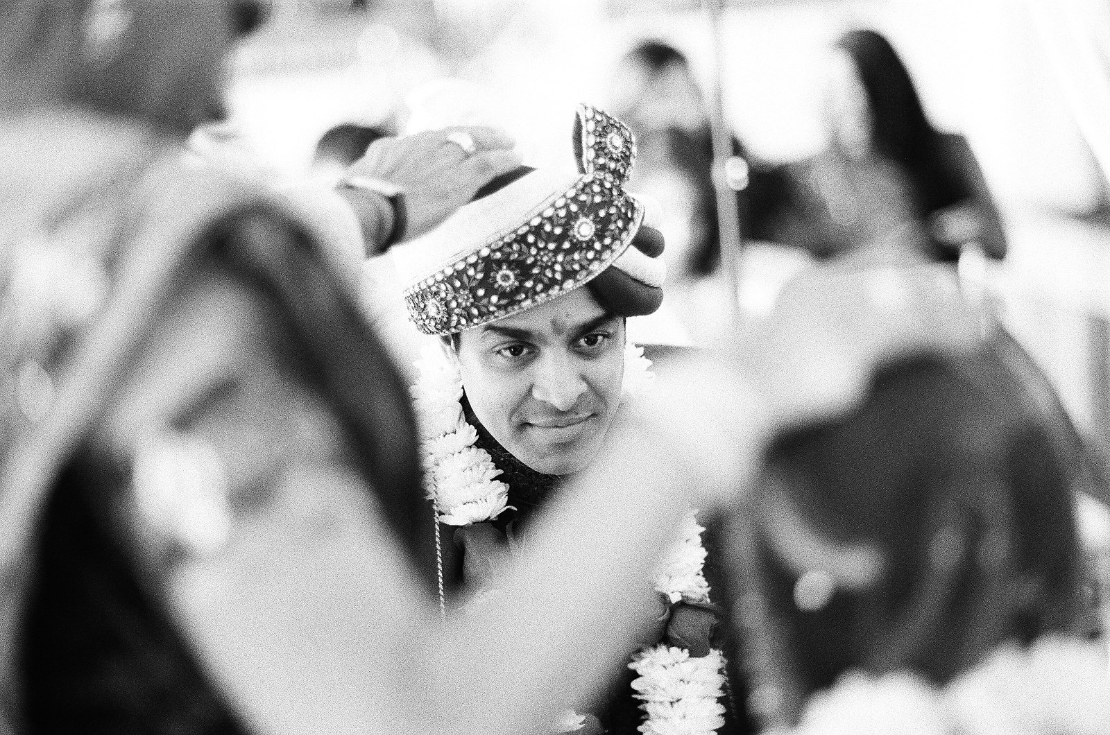 black and white photo of groom looking at bride during indian wedding ceremony