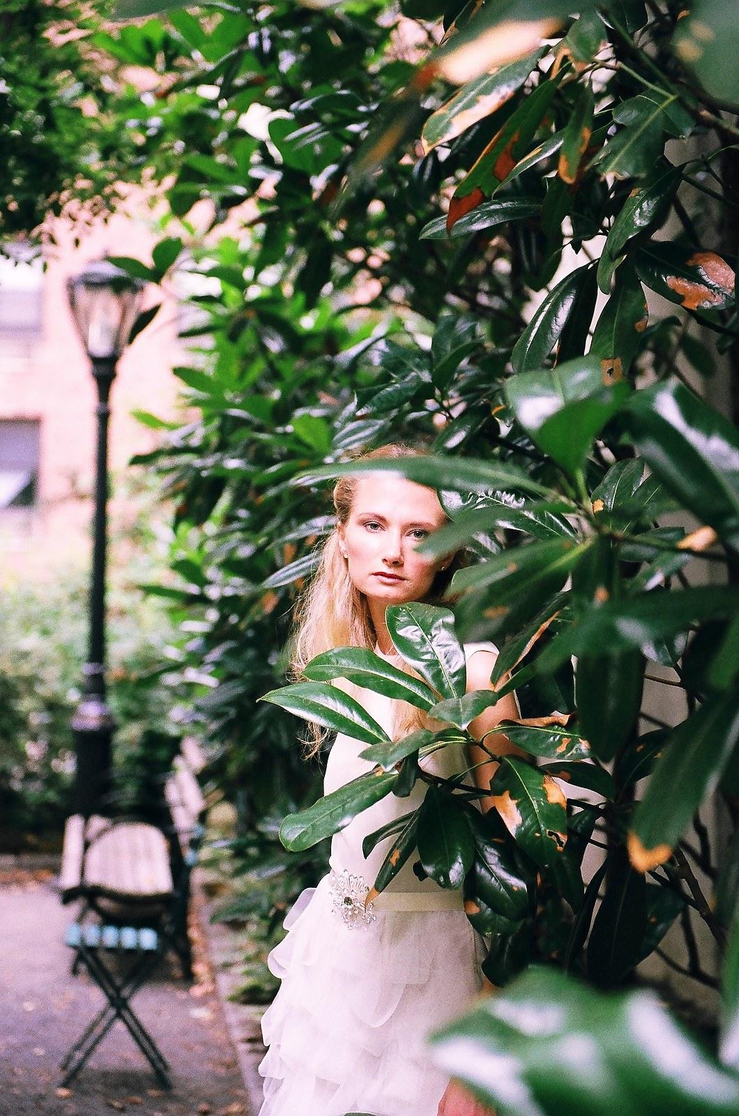 fine art photo of bride in dress hidden behind leaves in garden