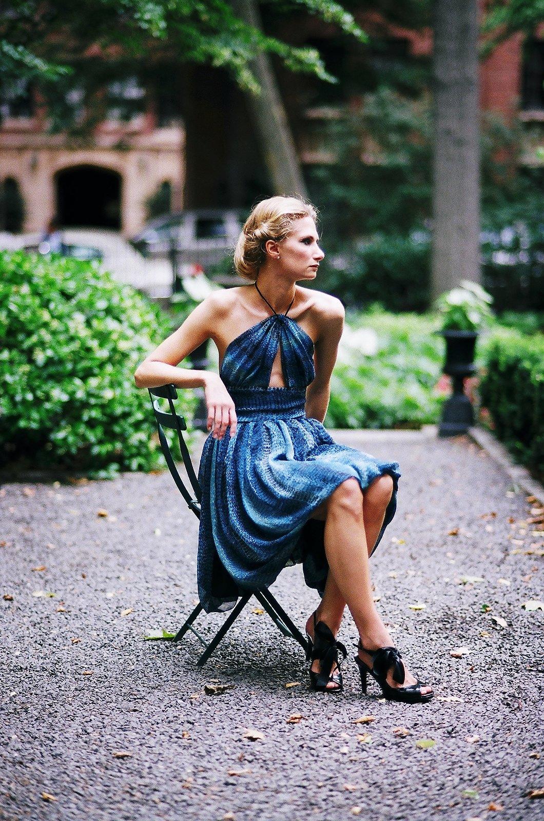 woman in blue toned dress sitting pretty in garden