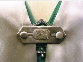 The cloak's fastener has hand-sewn buttonholes and silver embroidery.