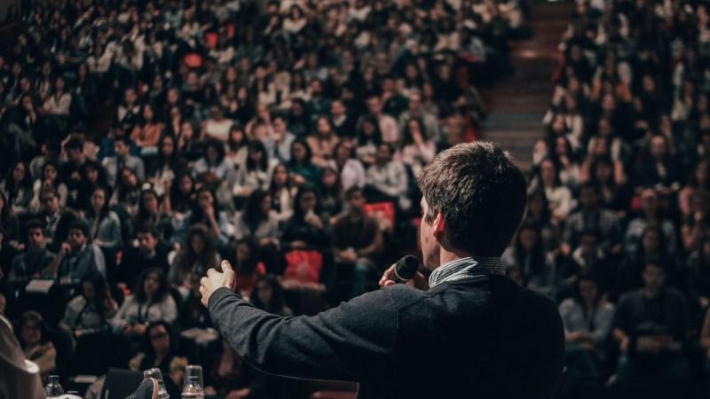 Man som pratar inför publik