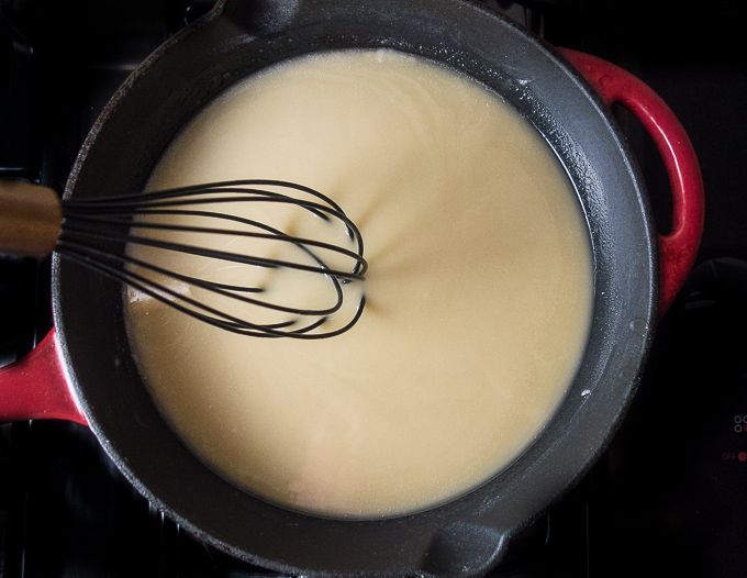 how to make roux: a step-by-step guide, white roux being whisked in a cast iron skillet