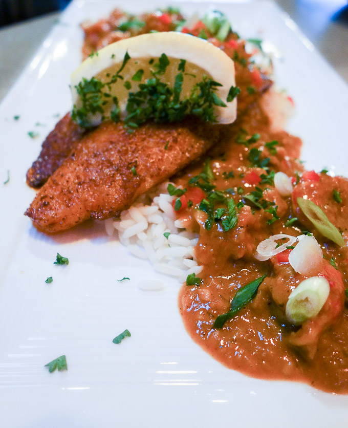 best cajun food in downtown san diego baclened catfish topped with crawfish etouffee and green onions on a plate