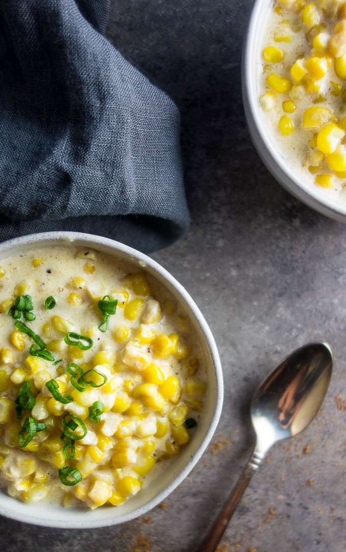 instant pot spicy creamed corn in a bowl garnished with green onion