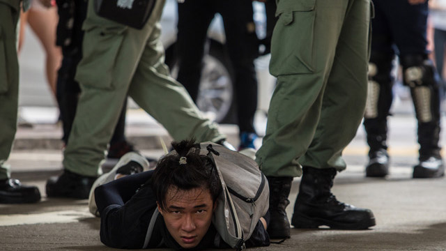 七月一日香港人上街抗议国安法,一名男子遭港警压制在地。(法新社)