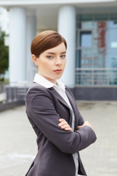 22489055 - businesswoman stands in front of office building with arms crossed