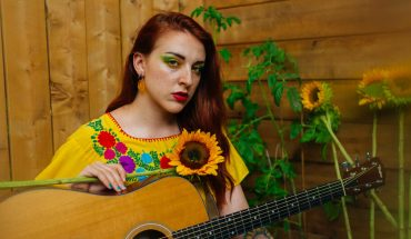 Holly Clausius promo photo. Holly is sitting amongst sunflowers wearing a bright yellow top and yellow makeup while holding her guitar