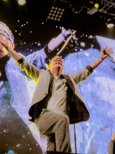 Torquil Campbell of the band Stars on stage with his arms thrown up in the air above him. He is holding a microphone in one hand and smiling.