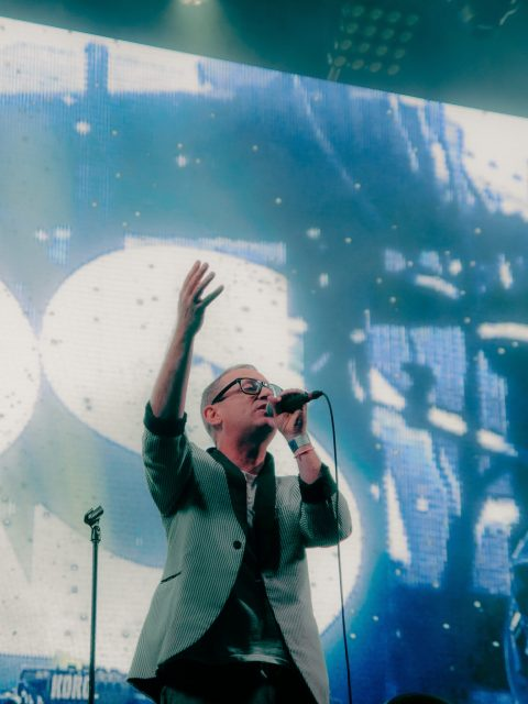 Torquil Campbell of the band Stars singing on stage. Behind him there is a screen that says Stars in bright white letters and blue lights.
