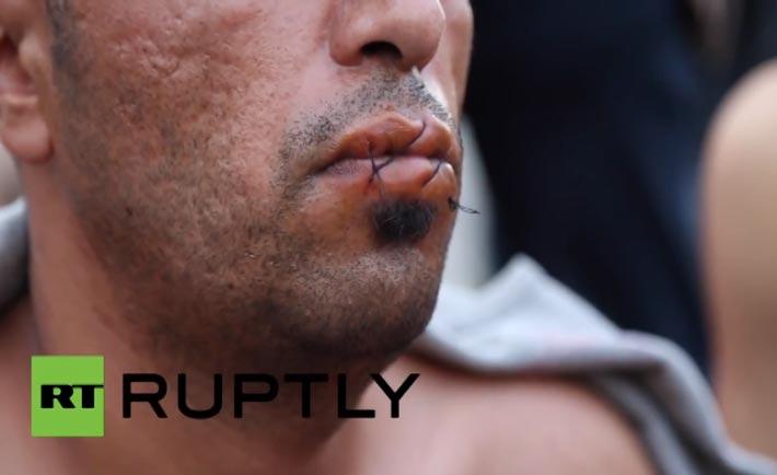 Rifugiati iraniani si cuciono bocca