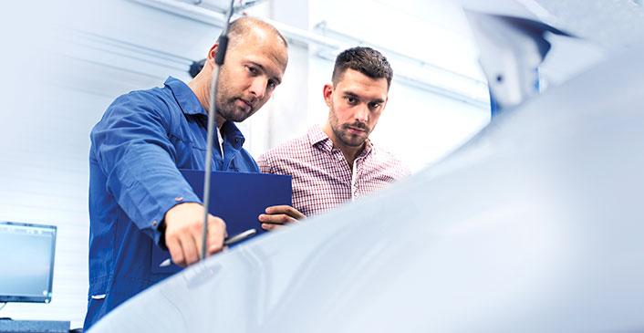 Werkstatt-Meister erklärt Kunden den Reparatur-Bedarf.