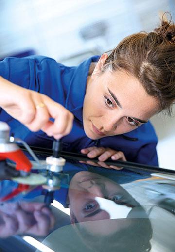 Mechanikerin beim Verkleben der Windschutzscheibe