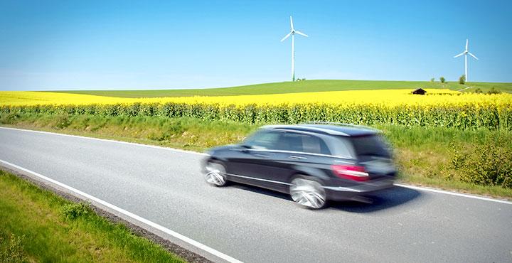 Auto auf Straße vor Rapsfeld, im Hintergrund Windräder