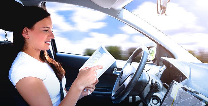 Frau liest in selbstfahrendem Auto ein Buch