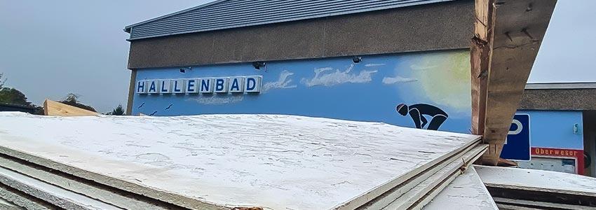 """Das Bild zeigt einen gefüllten Schutcontainer auf dem Parkplatz vor dem Eingang des Hallenbades in Oedelsheim. Im Hintergrund ist der Schriftzug """"Hallenbad"""" zu lesen."""