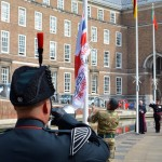 A bugler from 1RIFLES salutes as the Armed Forces flag is hoisted outside Bristol's City Hall.