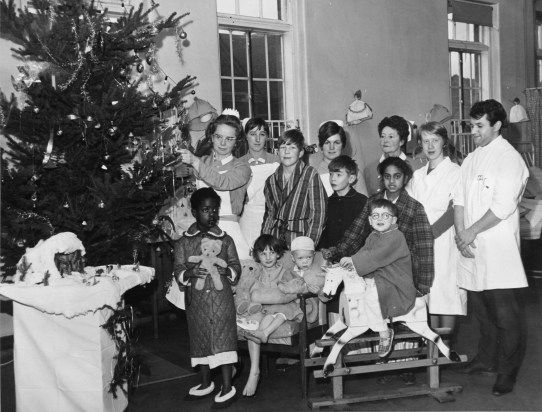 "Staff and children at Hallam Hospital, Children's Ward C1, 1967. Nurse Sister Charles is by the tree. Ivan Walker was there as Father Christmas. His wife Edna was a nurse at Hallam on the Children's Ward for 22 years (third from right). Ivan Walker told us: ""She only went for a month to start with. What made her day was seeing the children who had come in sick and very poorly and those same children go out again well and waving goodbye. She was originally a commercial artist at Kenrick & Jefferson before she became a nurse. They used to decorate the ward every Christmas with a theme – circus, for example, with stand up models of tigers and lions and Mickey Mouse and that sort of thing."" Courtesy of Ivan Walker."