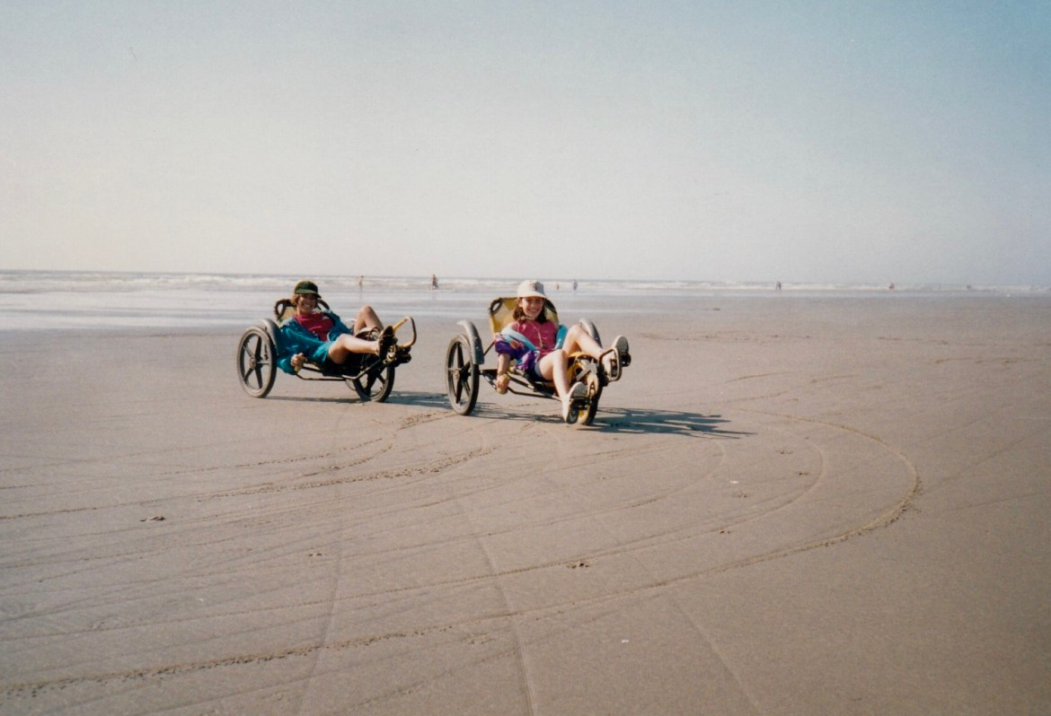 Two girls riding tricycles on the beach