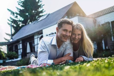 Happy couple lying on grass in the garden of their country house