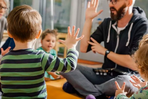 Child raising hand while singing with others and teacher in kindergarten