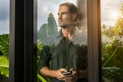 Handsome man standing behind glass facade of design house holding smartphone surrounded by lush tropical garden