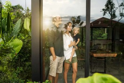 Garden view of parents with their young son looking outside of their design house surrounded by lush tropical garden