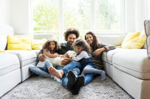 Happy family with dog sitting together in cozy living room