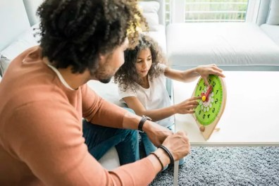 Father helping daughter learn reading the clock