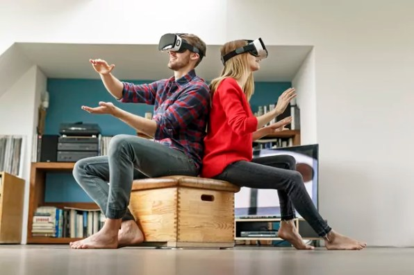 Young couple at home sitting on box wearing VR glasses