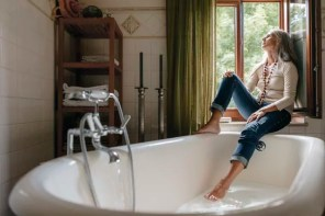 Woman sitting on window sill in the bathroom looking out of window
