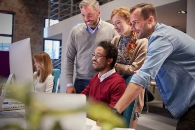 Colleagues looking over shoulder of young man working in modern office