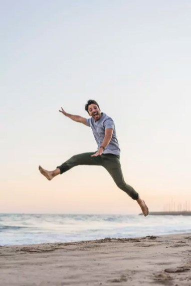 Happy young man jumping in the air on the beach at sunset