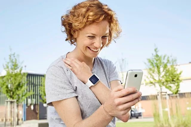 Happy young woman with smartwatch using smartphone in urban surrounding