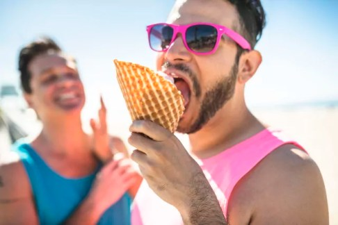 Portrait of man with pink sunglasses eating icecream