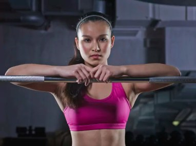 Portrait of young woman leaning on barbell
