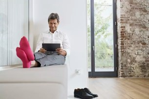 Businessman with pink socks using tablet in office