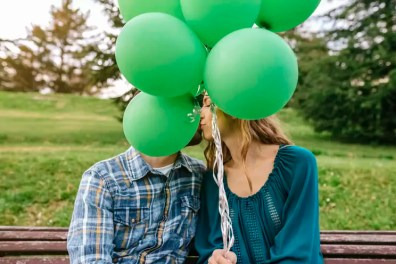 Young couple kissing behind green balloons