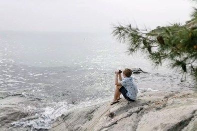 Greece, Chalkidiki, boy with binoculars sitting on rock looking at the sea