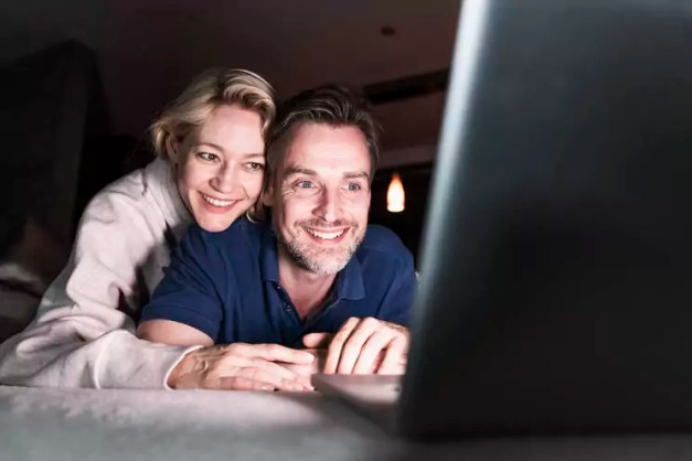 Happy couple lying on couch at home looking at laptop