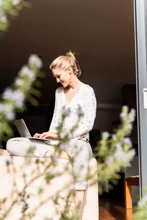 Smiling mature woman sitting at open terrace door using laptop