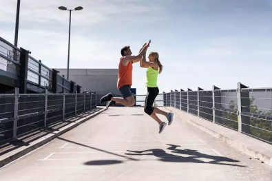 Jogging couple jumping for joy, highfiving